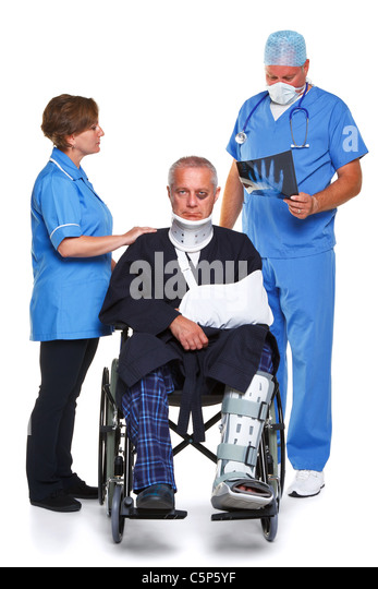 Photo of a doctor in scrubs examining an x-ray of the man in the wheelchairs hand - Stock Image