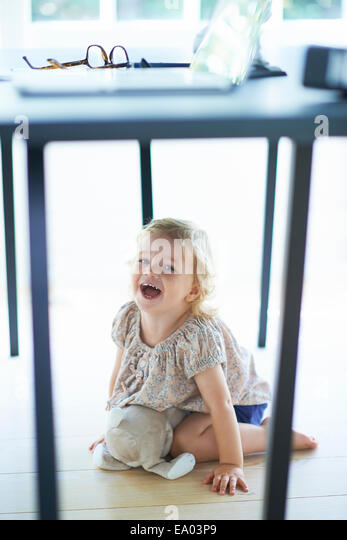 Female toddler hiding and laughing under dining room table - Stock Image