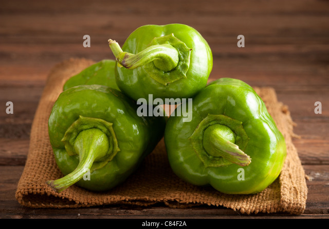 Three Green Bell Peppers on Jute and Wood - Stock Image