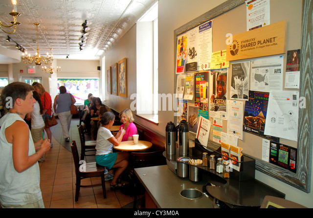 New Hampshire Portsmouth Market Square Congress Street Starbucks Coffee community bulletin board woman looking notices - Stock Image