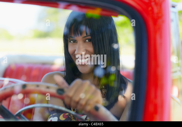 young adult brunette woman driving convertible red car and looking at camera. Horizontal shape, front view - Stock Image