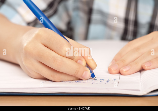 Close up of a hand of a pupil writing homework or examination - Stock Image