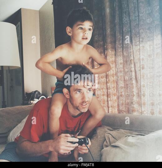 Father And Son Playing Video Game At Home - Stock Image