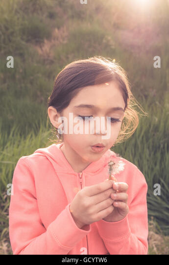 Young girl at sunset blowing on a dandelion and making a wish. - Stock Image