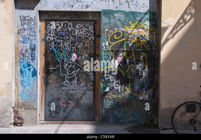 A doorway and wall in a narrow street covered with graffiti in Florence, Italy. - Stock Image