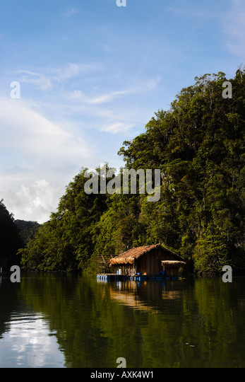 building in water tropical exotic trip vacation trees sky clouds blue white green brown reflection - Stock Image