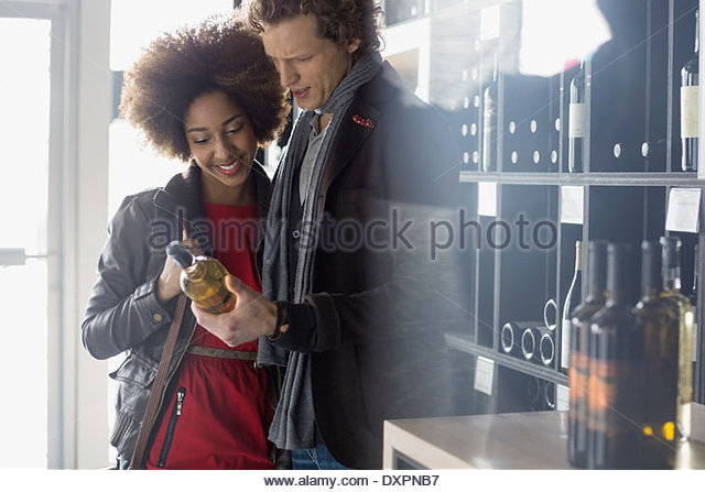 Couple reading label on bottle in wine store - Stock Image