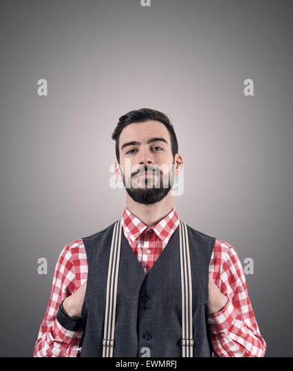 Desaturated portrait of young bearded hipster with hands pushed in his vest over dark gray studio background with - Stock-Bilder