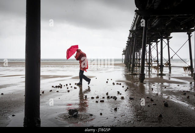 Saltburn by the Sea, North Yorkshire, England, UK. 8th Aug, 2017. UK weather: Yes it`s August! A man walks under - Stock Image
