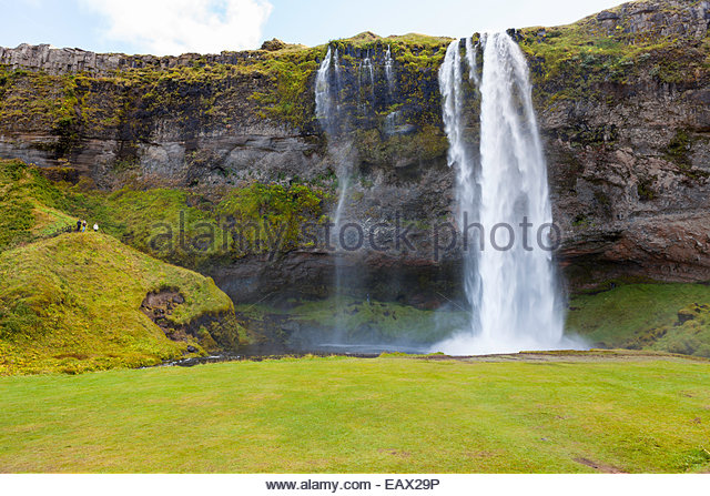 Seljalandsfoss waterfall cascading over a cliff in a landscape of electric green vegetation. - Stock-Bilder