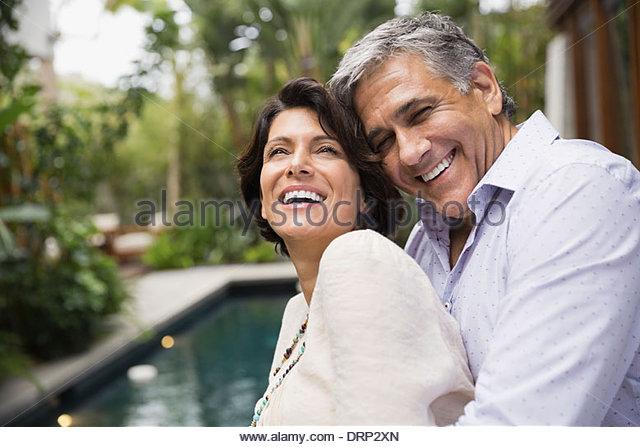 Mature couple embracing outdoors - Stock Image
