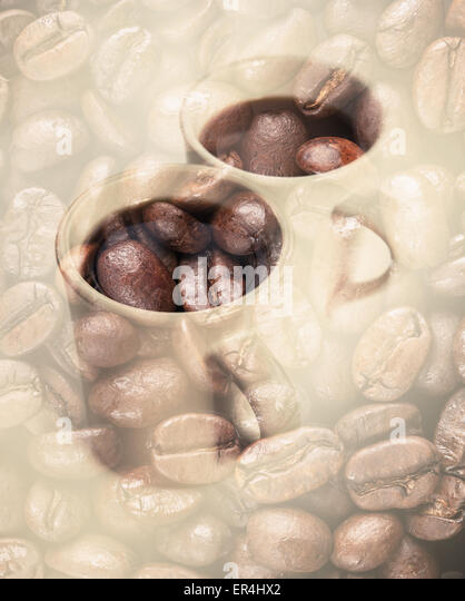 Two white coffee cups over dark rusted coffee beans texture. Double exposure photo with vintage style tonal photo - Stock Image