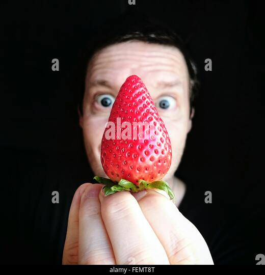 Portrait Of Man Holding Strawberry Against Black Background - Stock Image