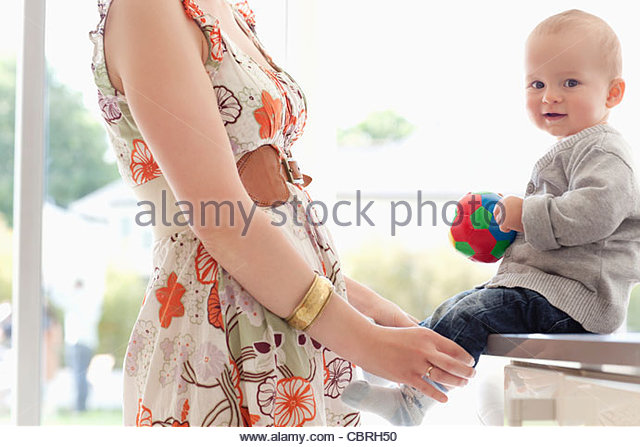 Mother standing with baby holding ball - Stock Image