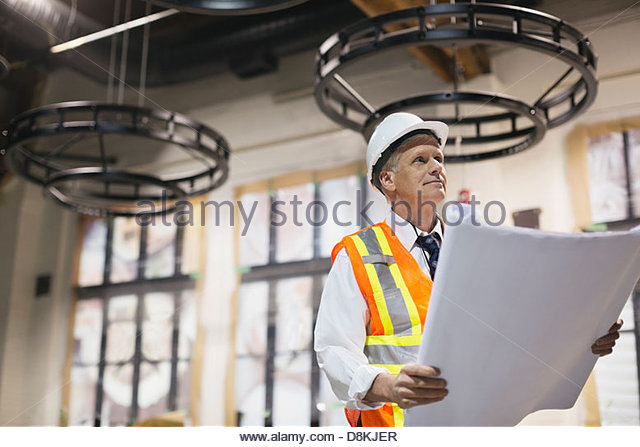 Male architect with blueprint at construction site - Stock-Bilder