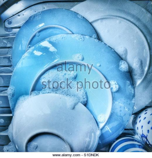 Washing dishes and pots in a pile on draining board - Stock Image