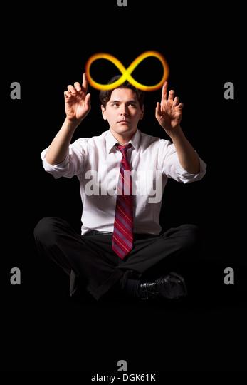 Businessman touching illuminated infinity symbol - Stock Image
