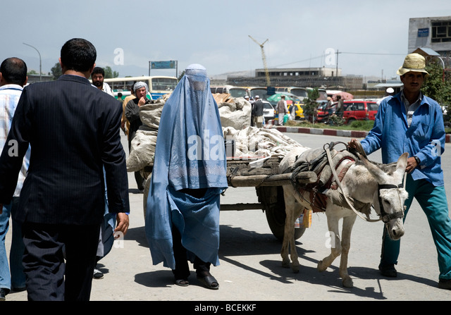 A mix of clothes and cultures from business suit to blue burqa to donkey cart in a busy Kabul street, Afghanistan's - Stock-Bilder