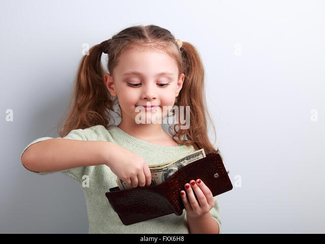 Cute small kid girl taking dollars from mother wallet and looking happy on blue background - Stock Image