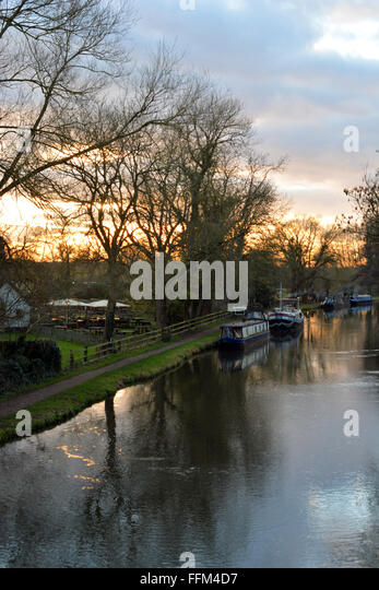 Canal flowing with a beautiful sunset behind the Cunning Man, Burghfield, Reading, Berkshire, UK. Charles Dye / - Stock Image