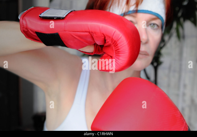 a woman who trains with red boxing gloves and white camisole - Stock Image