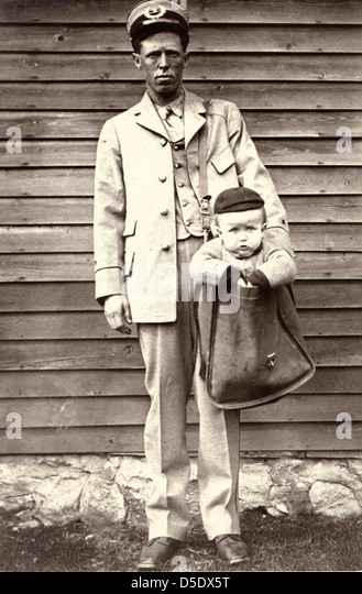 Uniformed Letter Carrier with Child in Mailbag - Stock Image