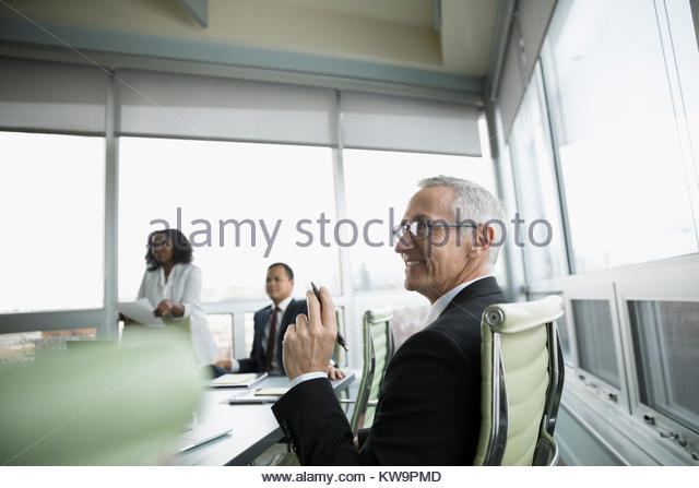 Smiling mature businessman listening in conference room meeting - Stock Image