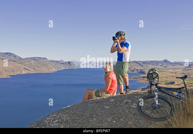 Young couple stop to take pictures of view while mountain biking over Kamloops Lake just west of Kamloops British - Stock Image