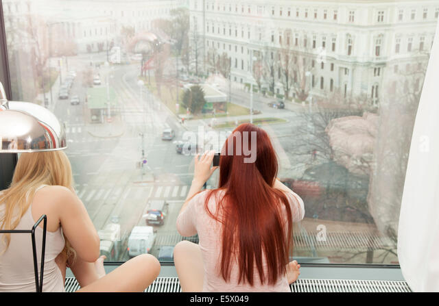 Young woman taking photograph by hotel window with view, Vienna, Austria - Stock Image