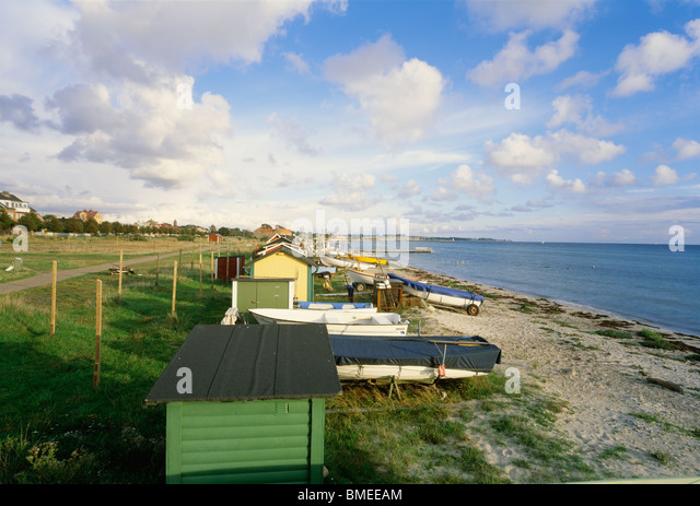 Beach huts and fishing boats on beach - Stock Image