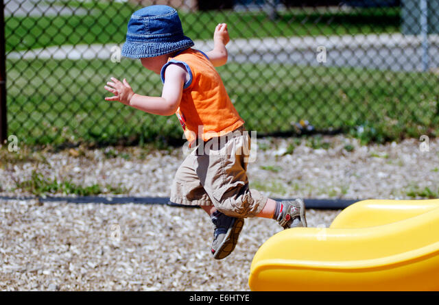 A two year old boy jumping from a slide - Stock Image
