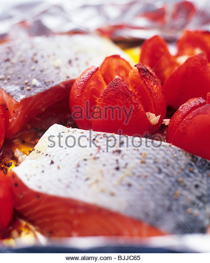 Salmon fillet with tomatoes on aluminium foil - Stock Image