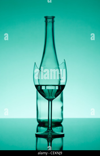 broken glass - in focus, and a bottle - out of focus - Stock-Bilder