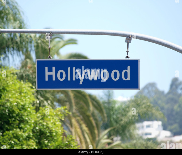 Hollywood Blvd sign with palm tree backdrop. - Stock Image