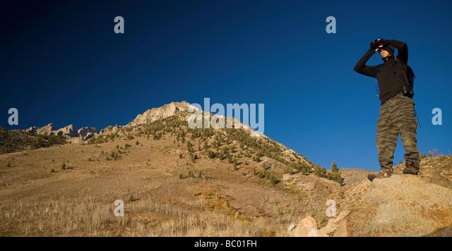 Hiker surveys his surroundings through binoculars. - Stock Image