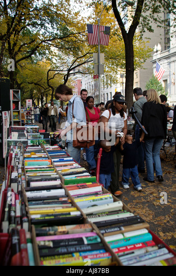 Strand Bookstore outdoor sidewalk sales tables filled with books on Fifth Avenue in Central Park Manhattan New York - Stock Image