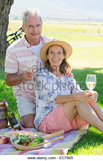 Senior couple sitting on picnic blanket - Stock-Bilder