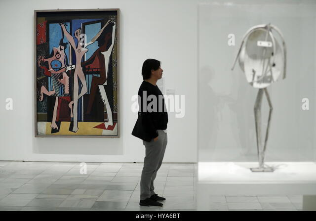 A visitor stands next to the work of art 'Three Dancers', by Spanish artist, Pablo Picasso, during the presentation - Stock Image