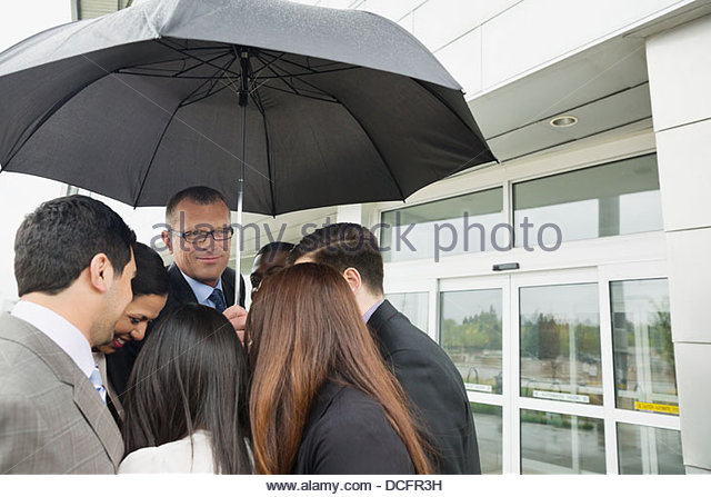 Group of business people sharing one umbrella - Stock Image