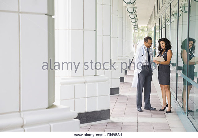 Doctors reviewing information outdoors - Stock Image