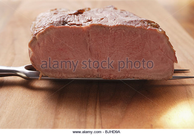 Roast beef sirloin on meat fork - Stock Image
