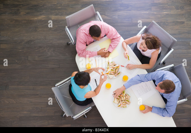 Four businesspeople at boardroom table with sandwiches - Stock-Bilder
