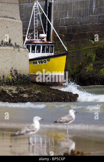 A yellow fishing boat in Newquay Harbour. - Stock Image