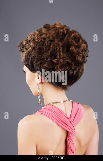 Frizzy Hair. Rear View of Brown Hair Woman with Festive Hairstyle - Stock Image