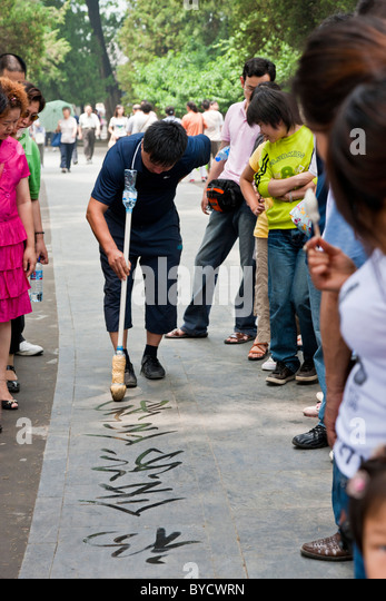 Chinese man practicing street calligraphy in the grounds of the New Summer Palace, Beijing, China. JMH4796 - Stock Image