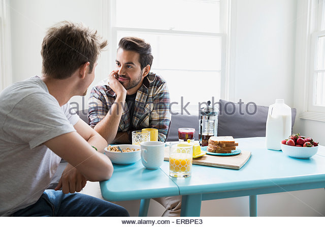 Homosexual couple face to face at breakfast table - Stock Image