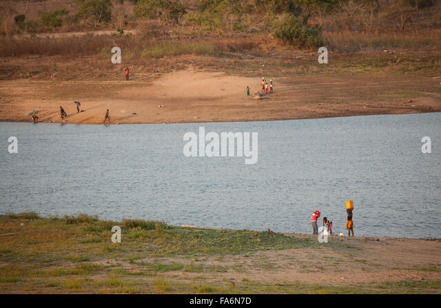 Residents draw water from the Muecula River near the Nacala Dam and reservoir in Nampula Province, Mozambique. - Stock Image