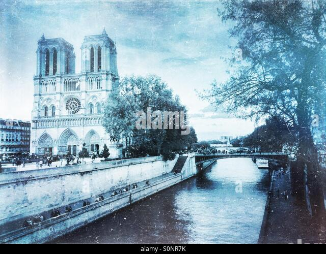 View of Notre Dame Cathedral from Petit Pont across the Seine River. Frosty, winter-inspired vintage paper texture - Stock Image