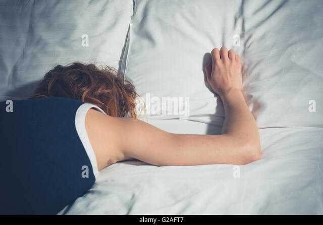 A young woman wearing a dress is passed out on a bed - Stock Image