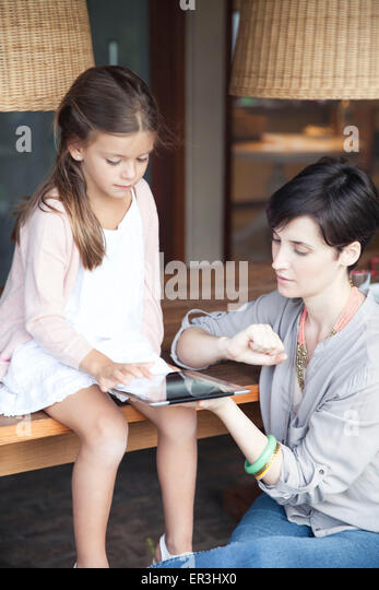 Mother and young daughter using digital tablet together - Stock-Bilder